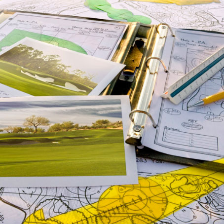 A binder and golf course designs.
