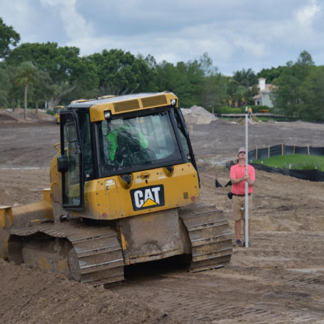A small cat working to shape dirt on golf course
