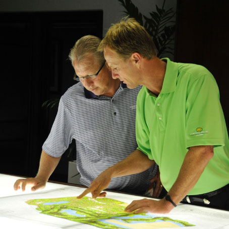Two standing men examining design plans